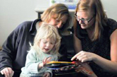 Graduate student Abigale Stangl (right), a CU-Boulder doctoral student and a volunteer at the Anchor Center for Blind Children in Denver, shows Isabella Chinkes and her mother, Linda, a 3D version of Goodnight Moon. Photo by Casey Cass, University of Colorado