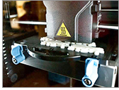 Multiple 3D objects being printed a layer at a time using extruded molten ABS material