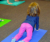 A child practices cat/cow pose during the Fayetteville (N.Y.) Free Library's Yoga Storytime. Photo by Katie Kaczorowski
