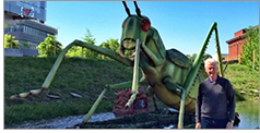 Former President Bill Clinton stands next to a giant grasshopper outside the Clinton Presidential Library in Little Rock, Arkansas